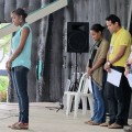 Young woman at microphone reciting prayer