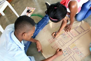 Young man and woman drawing a map on a large sheet of paper
